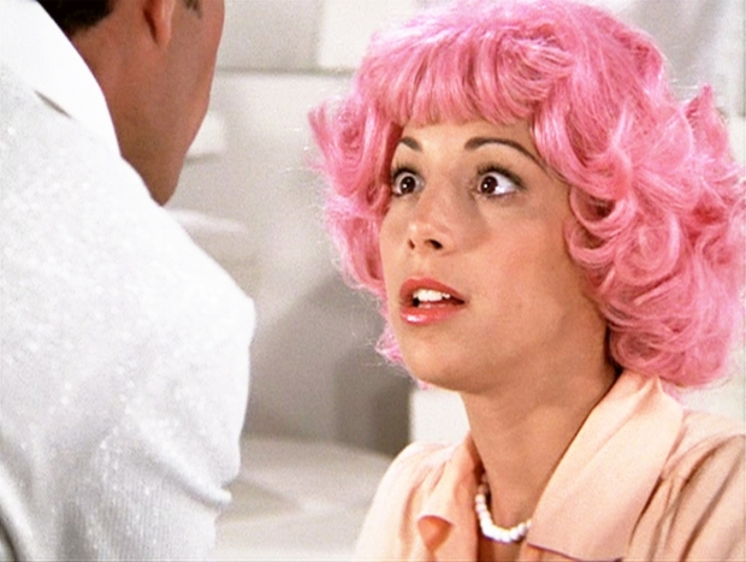 The image is from Grease. Frenchy stares at Teen Angel, sporting a pink curly bob.