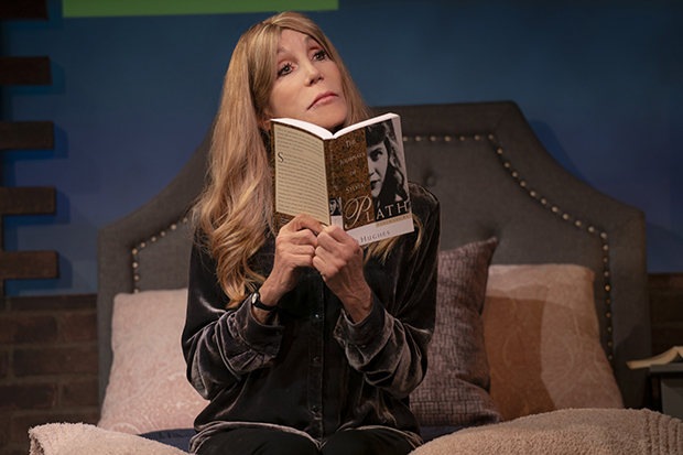 Playing her younger self, Barra Grant holds up a book by Sylvia Plath in Miss America's Ugly Daughter.